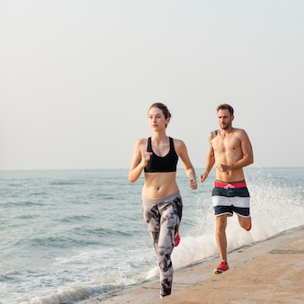 Healthy young couple running by the beach