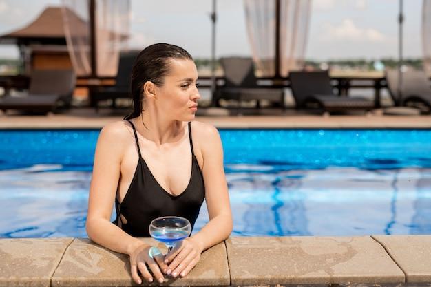 スパリゾートのスイミングプールで飲む水着で健康的な若い女性