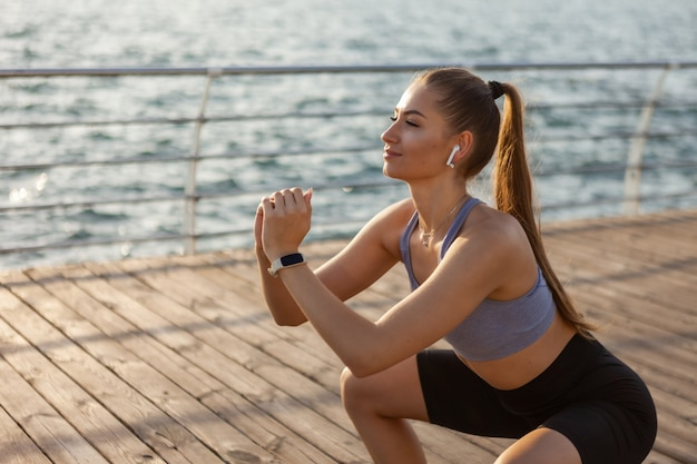 Healthy young fitness woman doing squat exercise on the beach at sunrise
