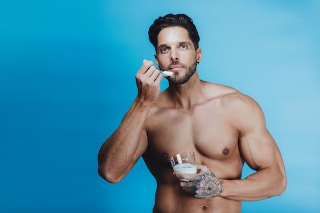 Healthy young man eats a yogurt on blue background