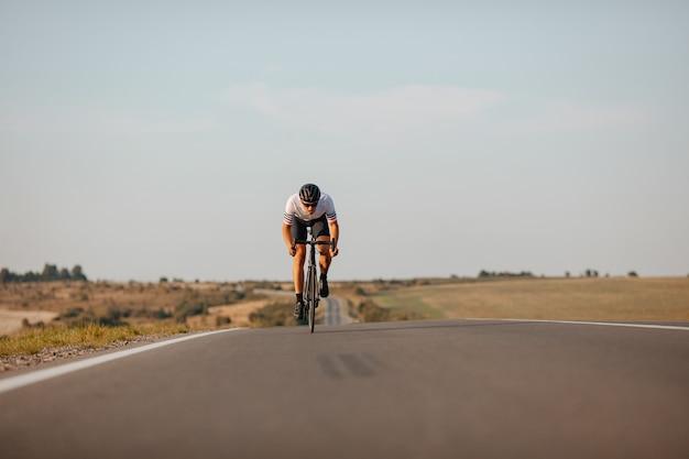 스포츠 의류, 보호 헬멧 및 아스팔트 도로에서 자전거 안경에 건강한 젊은 남자.