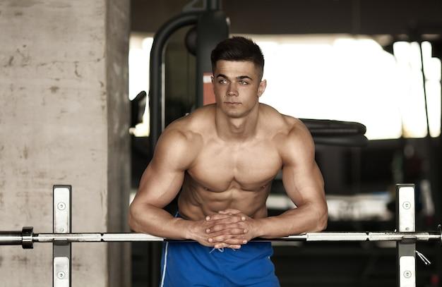 Здоровый молодой человек отдыхает в тренажерном зале здорового клуба после тренировки