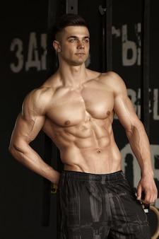 Здоровый молодой человек, сильный в тренажерном зале и разгибающий мышцы