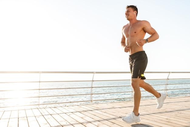 Здоровый молодой без рубашки спортсмен в наушниках работает