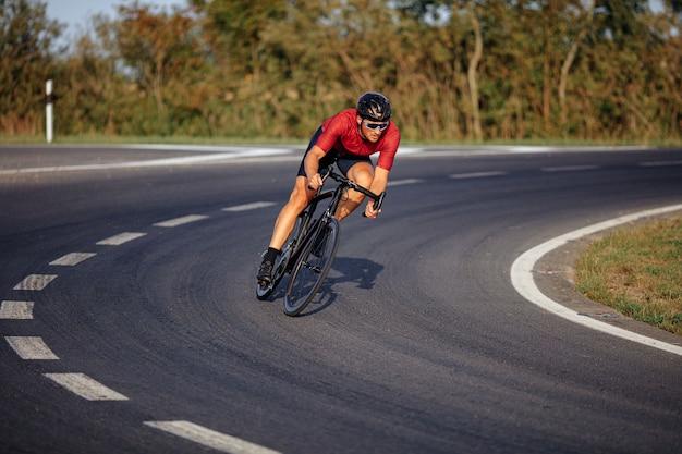 검은 헬멧과 야외 아스팔트 도로에서 자전거를 타는 보호 안경에 건강한 젊은 운동가