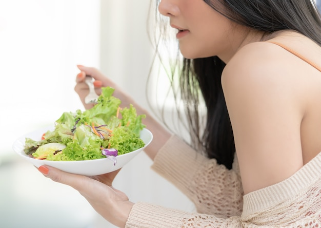 Healthy young woman eating green salad
