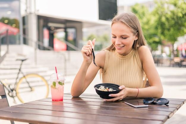 Здоровая молодая женщина ест салат на открытом воздухе в уличном кафе
