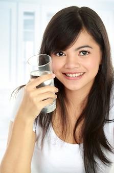 Здоровая молодая женщина держит стакан воды и улыбается