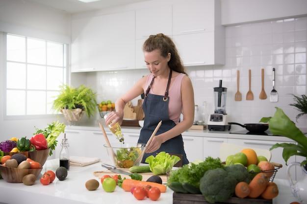 健康的な食事とサラダのために野菜を準備するキッチンで健康な若い女性
