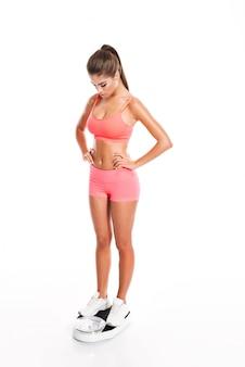 건강 한 젊은 여자 휘트니스 저울 무게 측정
