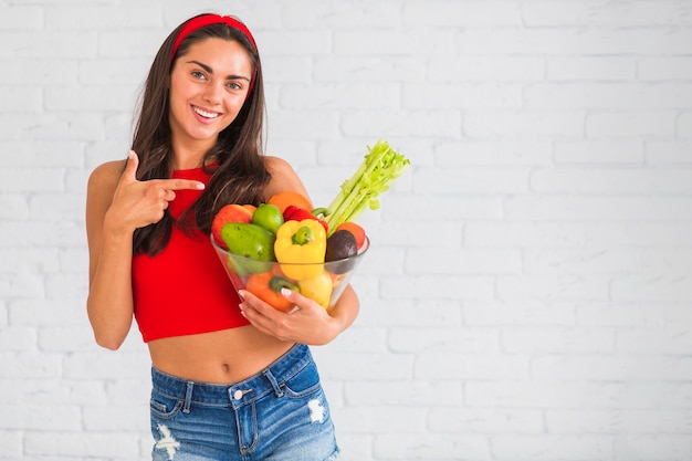 Healthy young woman pointing at bowl with fresh vegetables and fruits