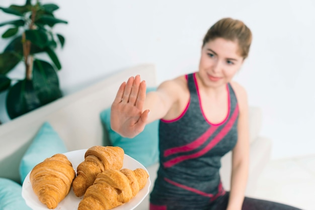 Healthy young woman showing no sign to the croissant