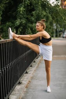 도시에서 야외에서 스트레칭 하는 건강 한 젊은 여자. 스포츠 천, 건강한 라이프 스타일과 핏