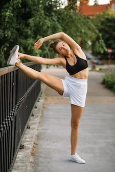 도시에서 야외에서 스트레칭 하는 건강 한 젊은 여자. 스포츠웨어, 건강한 라이프 스타일