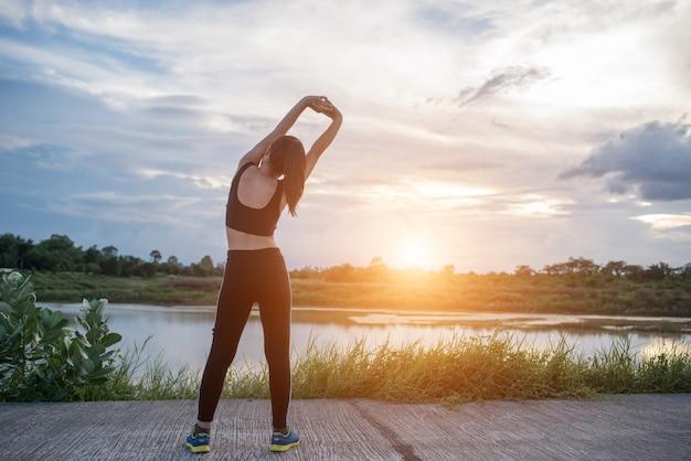 건강 한 젊은 여자는 공원에서 훈련 세션 전에 야외 운동을 워밍업.