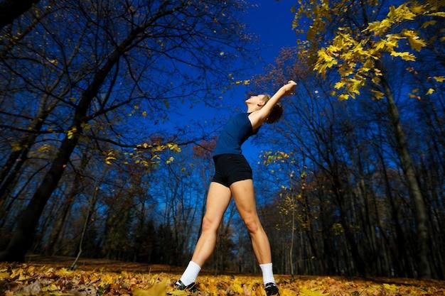 Здоровая молодая женщина нагревается, протягивая руки на улице, бег трусцой в парке.