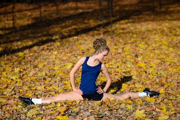공원에서 조깅 세션 야외 도로에서 그녀의 팔을 스트레칭 워밍업 건강 한 젊은 여자.