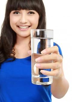 Здоровая молодая женщина с бокалом пресной воды