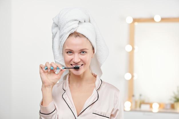 거울과 함께 아침에 욕실에서 그녀의 이빨을 칫솔질 건강한 젊은 여자