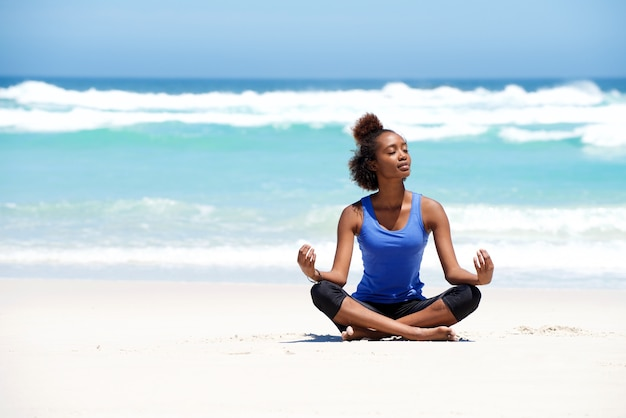 Healthy young yoga woman meditating at the beach