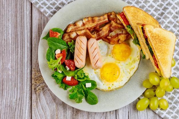 卵、サラダ、ブドウ、グリルチーズトーストなどの健康的な朝食。