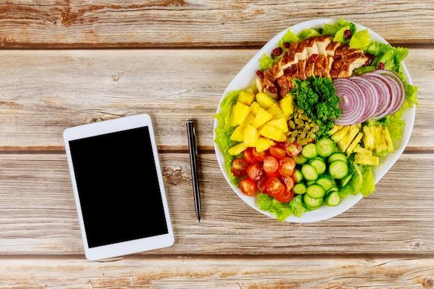 タブレットと木製のテーブルの上にペンで健康的なサラダ