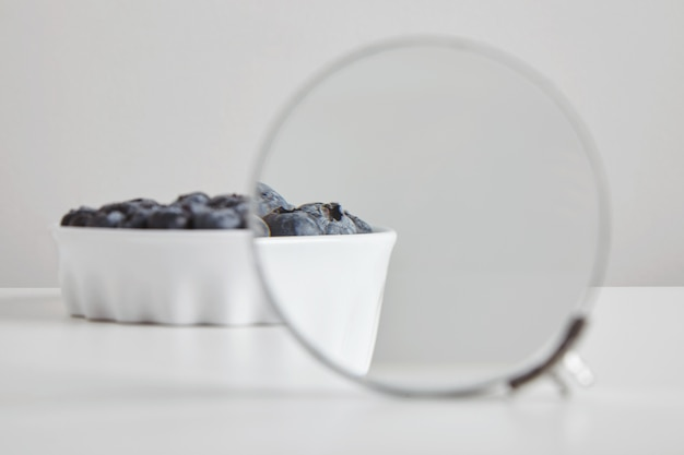 Heap of blueberry antioxidant organic superfood in ceramic bowl concept for healthy eating and nutrition isolated on white table, magnigied through binocular magnifier to see details