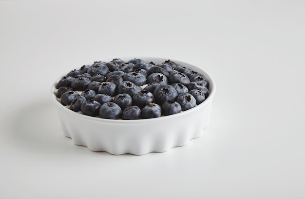 Heap of blueberry antioxidant organic superfood in ceramic bowl concept for healthy eating and nutrition isolated on white table