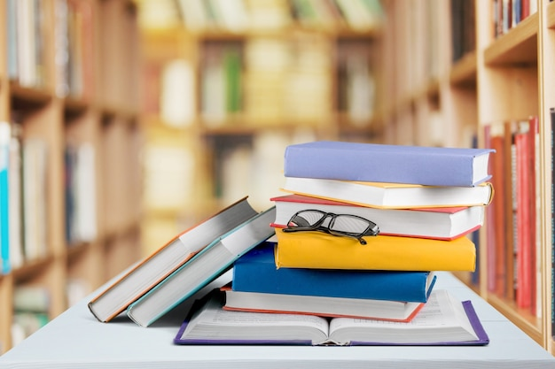 Heap of books with glasses on wooden table