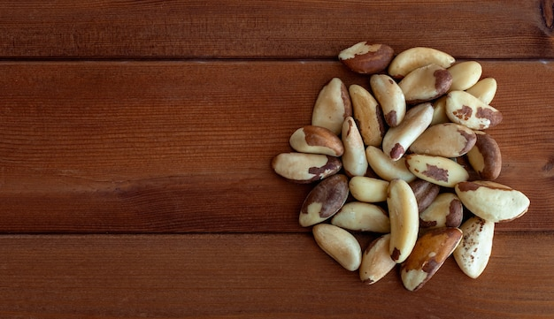 Heap of brazil nuts on the old wooden background close up top view. brazil nuts from bertholletia excelsa tree