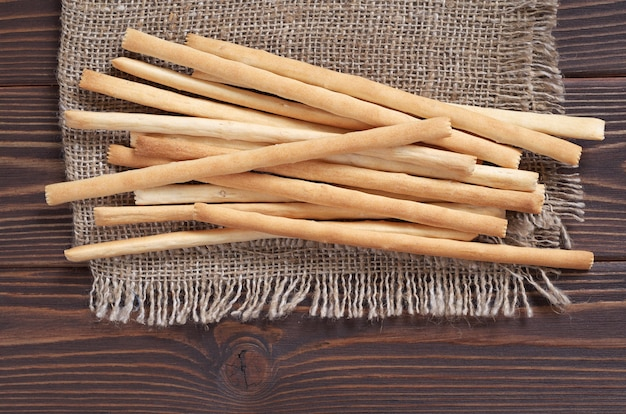 Heap of bread sticks on burlap is located on brown wooden background