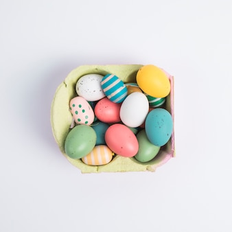 Heap of bright easter chicken eggs in container
