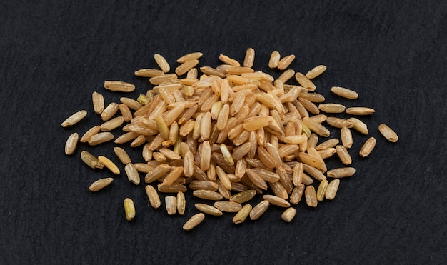 Heap of brown rice groats on black background