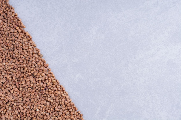 Heap of buckwheat arranged in a triangular shape on marble surface