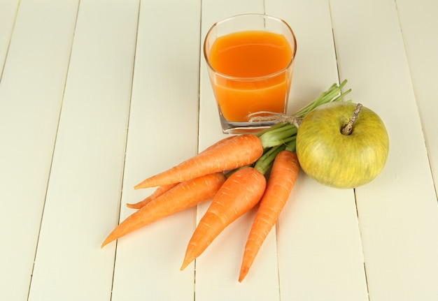 Heap of carrots and green apple, glass of juice, on color wooden table
