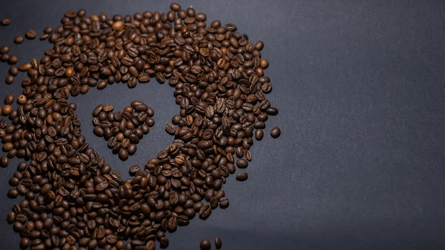 Heap of coffee beans on black background. coffee beans pile isolated on black background. culinary coffee background. heart shaped coffee beans top view