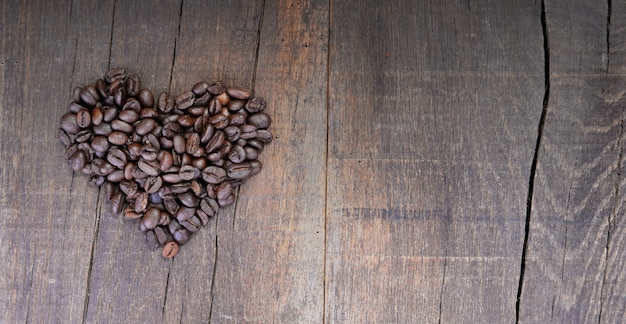 Heap of coffee beans forming a heart on a rustic plank with copy sapce at the right