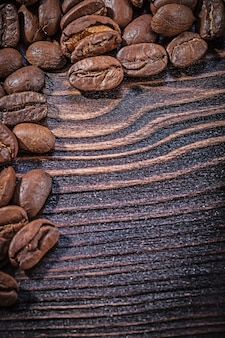 Heap of coffee beans on vintage wooden board top view