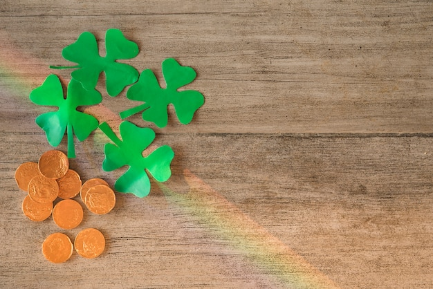 Heap of coins and green paper clovers on board