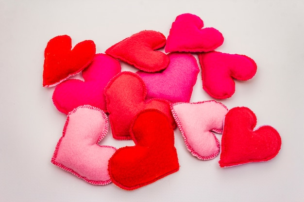Heap of colored felt hearts isolated on white background. valentines day or wedding romantic concept