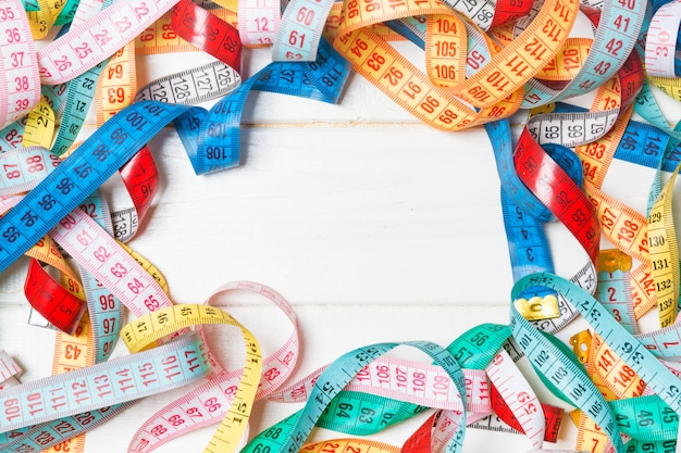 Heap of colorful measuring tapes in the form of frame