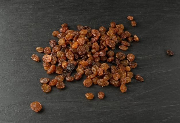 Heap of dark brown sweet raisins, dried grapes pile