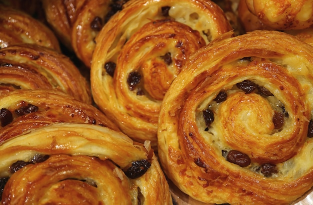Heap of delectable raisin cinnamon rolls lined up on the tray, selective focus