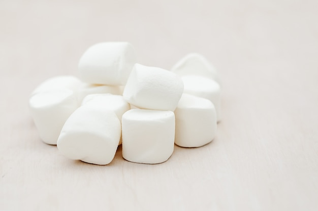 Heap of delicious white fluffy marshmallows on wooden background. winter food background concept.