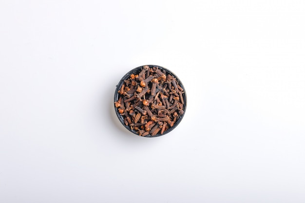 Heap of dried cloves in bowl,  on white background