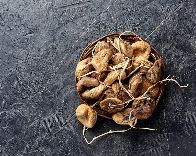 Heap of dried figs on black background with copy space.