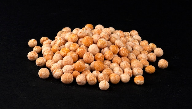 Heap of dried yellow pea isolated on black background, closeup