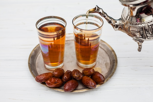 Heap of dry dates near cups of tea and teapot