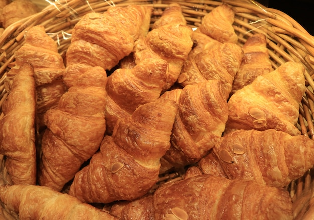 Heap of fresh baked almond croissant pastries in a basket, for background