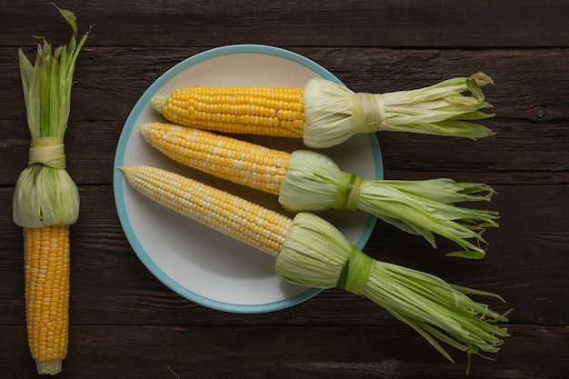 Heap of fresh raw corn on the cob on a wooden table, top view